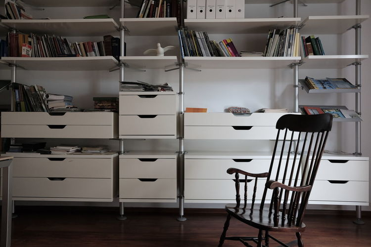 Empty rocking chair against books on shelf at home