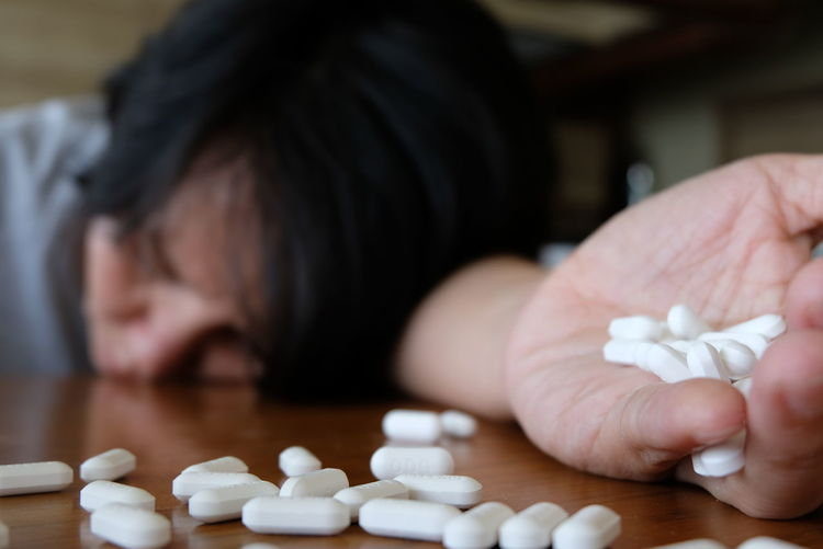 Close-Up Of Woman With Pills On Table