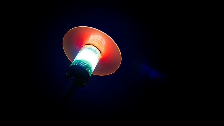 Low angle view of illuminated light bulb against black background
