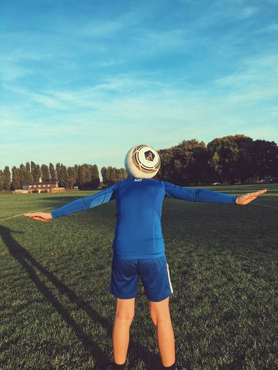 Caching the ball One Person Sky Cloud - Sky Plant Real People Leisure Activity Front View Lifestyles Unrecognizable Person Nature Casual Clothing Standing Day Field Obscured Face Blue Grass Land Outdoors