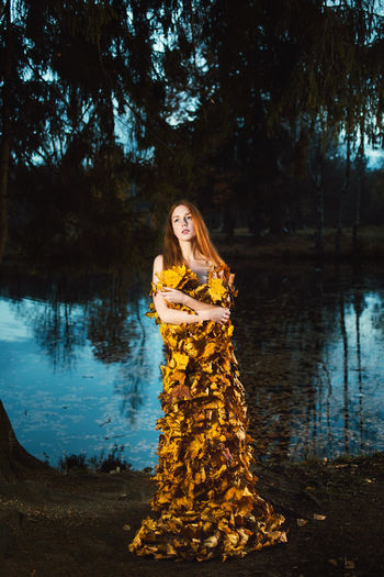 Thoughtful young woman covered with leaves standing by lake at forest during autumn