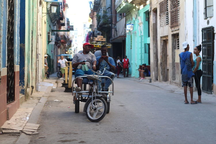 Rear view of people riding bicycle on street in city