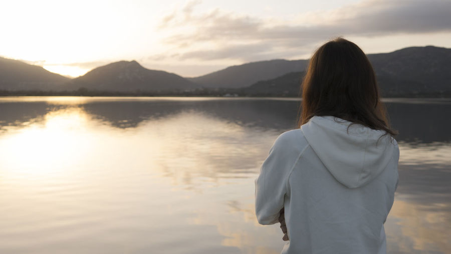 Rear view of woman standing by lake against sky during sunset