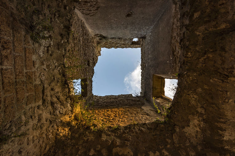 Old ruin building seen through hole in wall