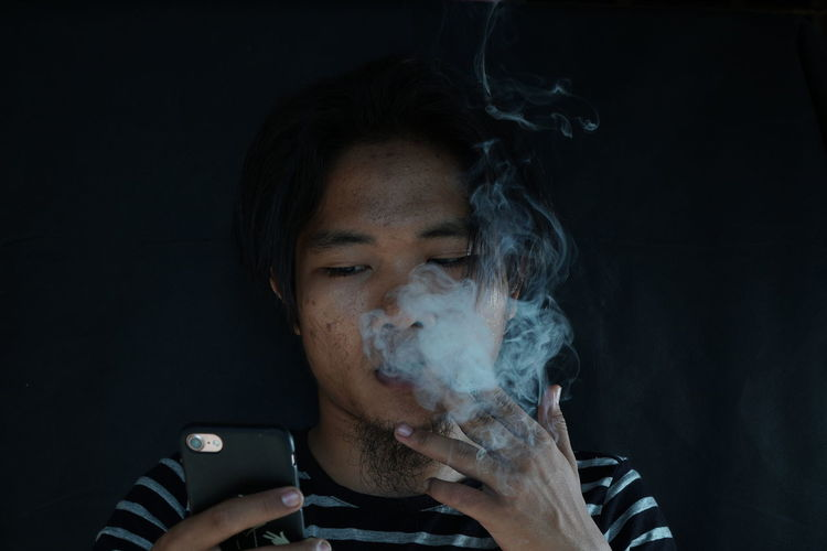 Close-up of young man smoking cigarette against wall