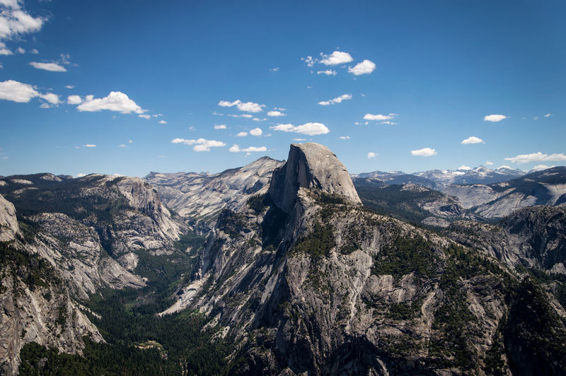 Scenic view over the mountains of the Yosemite National Park under a blue sky with few clouds Blue Blue Sky Clouds Day First Eyeem Photo Freedom Glacier Point Half Dome Hiking Horizon Over Land Landscape Mountain Mountains Nature No People Non-urban Scene Outdoors Rocks Rocky Summer Travel Traveling Tree Yosemite National Park