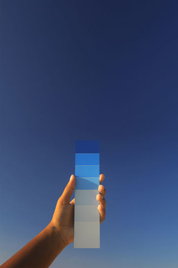 Close-up of hand holding color swatch against clear blue sky