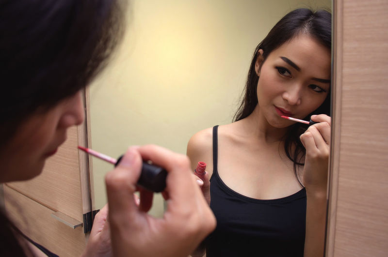 Woman Applying Lipstick While Looking Into Mirror At Home