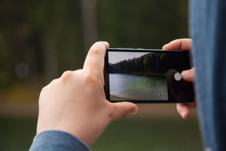 Cropped image of person photographing with mobile phone