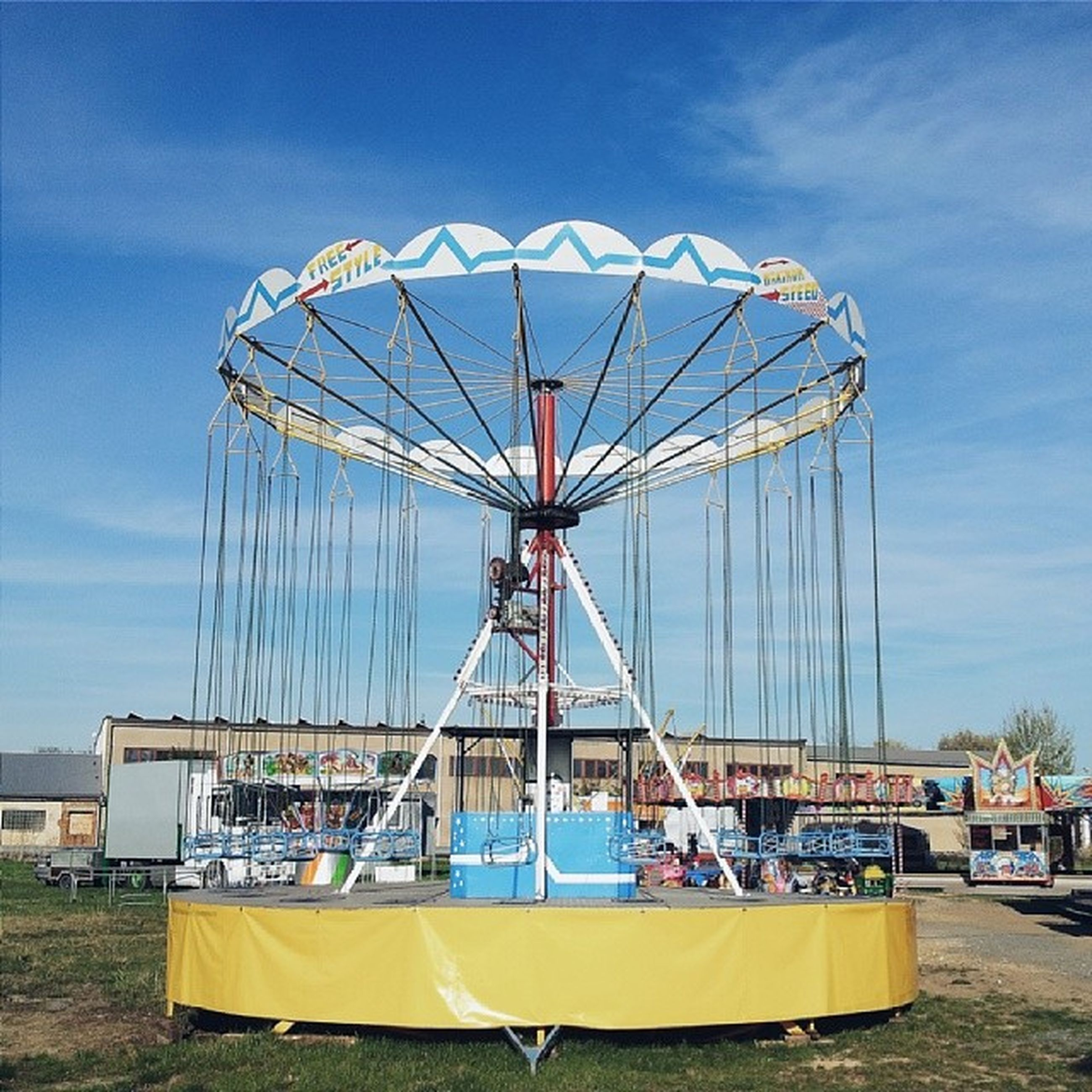 amusement park, amusement park ride, ferris wheel, sky, arts culture and entertainment, low angle view, blue, fun, cloud - sky, day, outdoors, built structure, enjoyment, sunlight, metal, cloud, leisure activity, beach, incidental people, no people