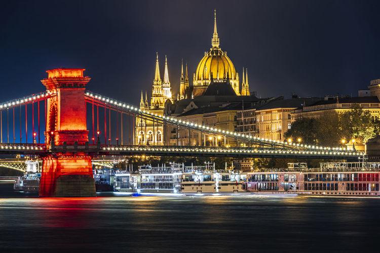 Illuminated bridge over river against hungarian parliament building at night