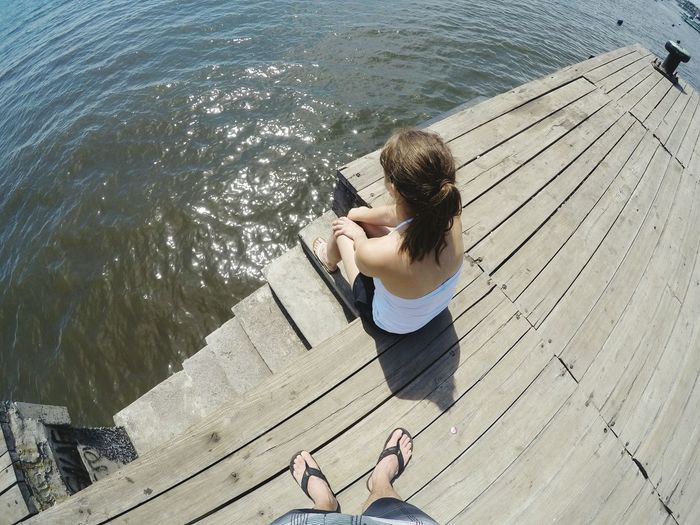 High angle view of woman photographing while standing on pier