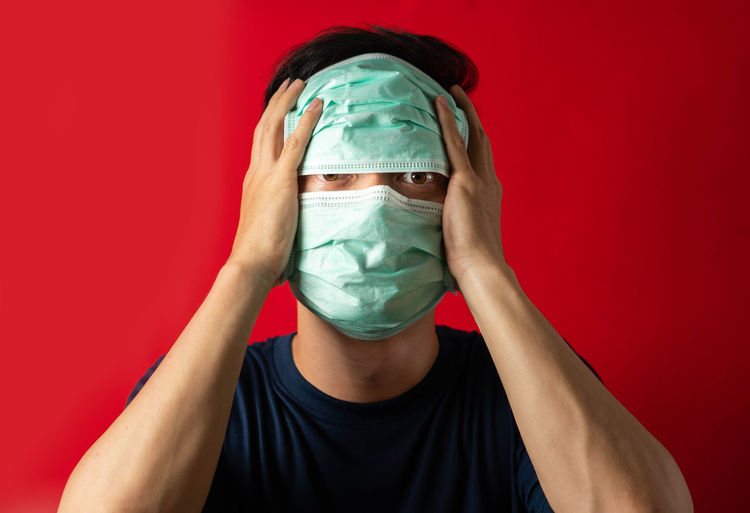 Portrait of person covering face against red background