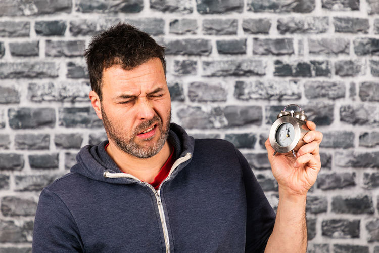 Portrait of man holding camera against wall