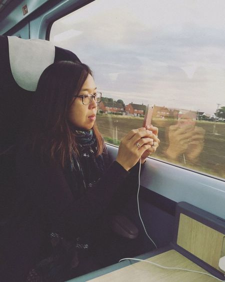 Woman Photographing Using Smart Phone In Train