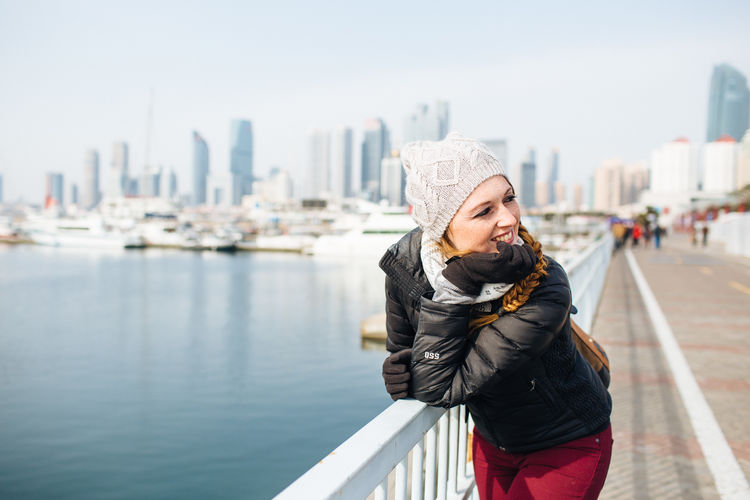 Young Woman Standing On Promenade By River In City During Winter