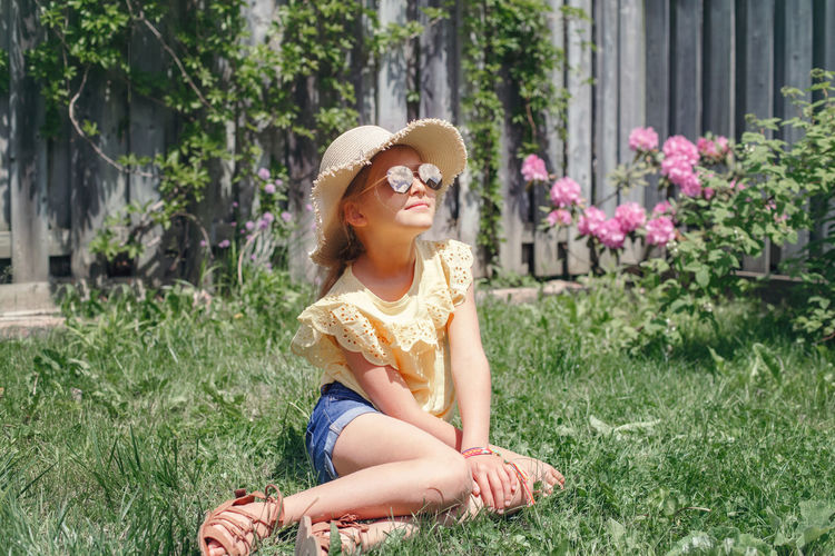 Girl sitting in grass at yard