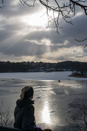 Rear view of girl standing on lake during winter