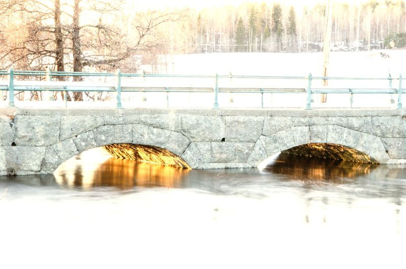 Arch bridge over river during winter
