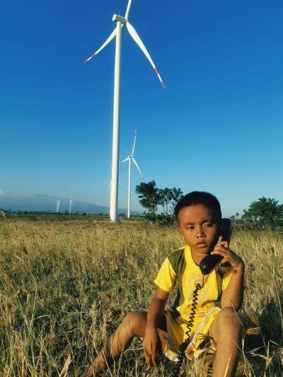 Boy holding telephone sitting on field against windmill