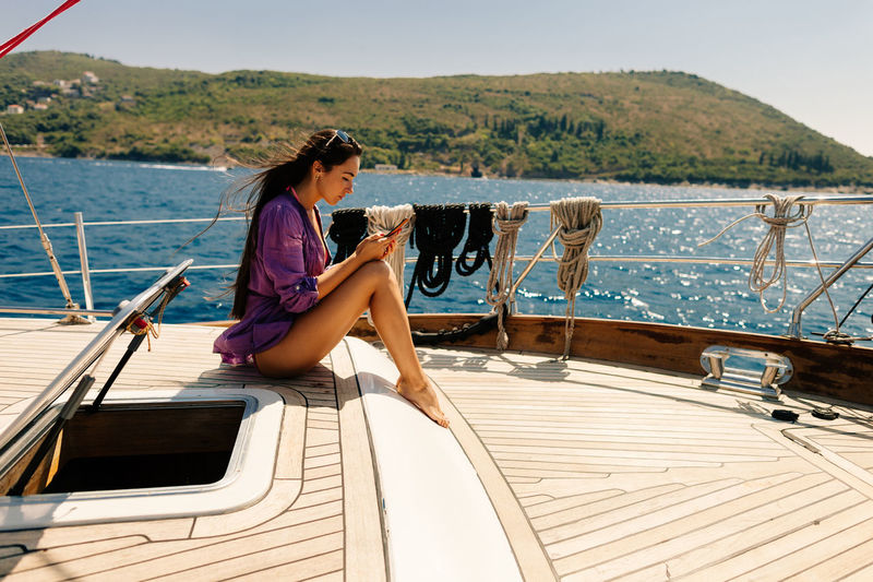 Young woman sitting on boat and sailing in sea against sky