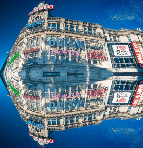 A reflected reflection of the Printworks Manchester Architecture Building Building Exterior Built Structure City City Life Communication Community Culture Famous Place Graffiti Human Settlement Manchester Mode Of Transport Modern Outdoors Printworks Puddle Reflection Residential District Street Text Transportation Vignette Western Script