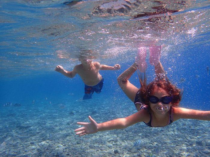 Siblings Swimming In Sea
