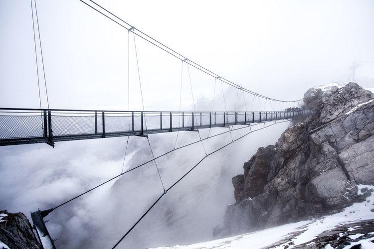 Narrow footbridge along rocky mountains
