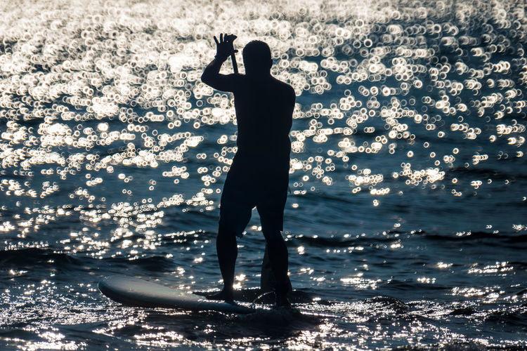 Silhouette man paddleboarding on sea