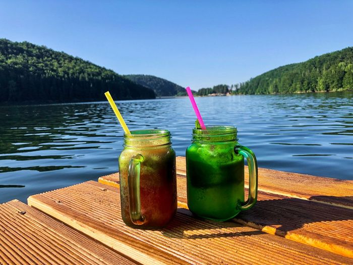 Two glasses of lemonade on wooden pontoon near the lake