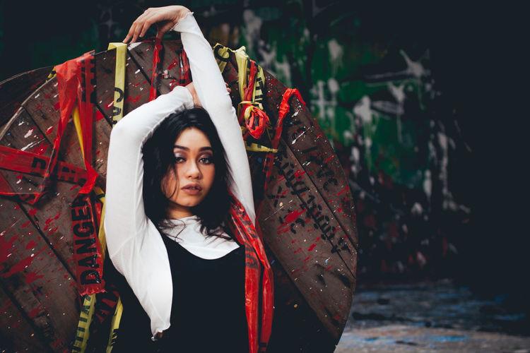 Portrait of female model posing wooden spool