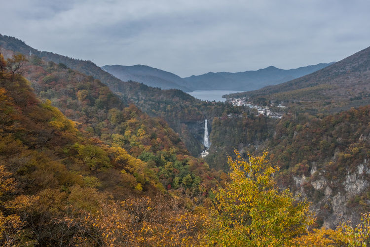 Scenic view of waterfall amidst tree and mountain against cloudy sky