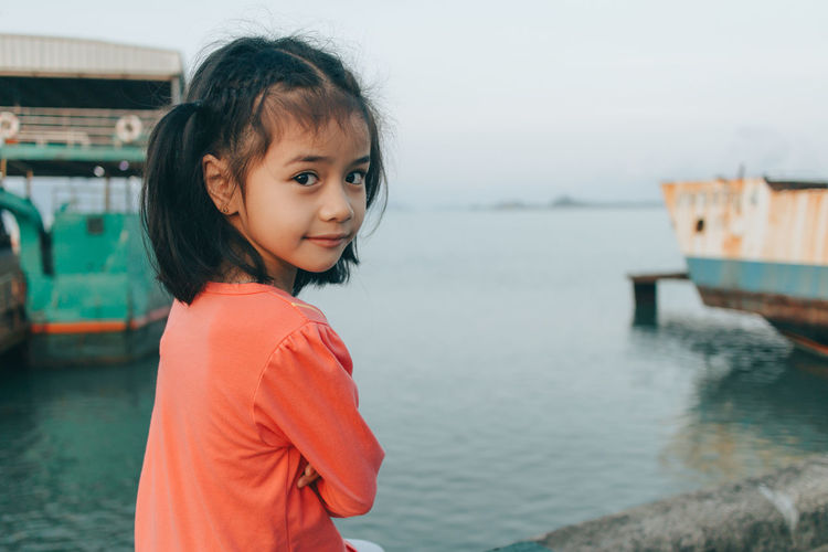 Portrait of smiling girl standing at sea shore
