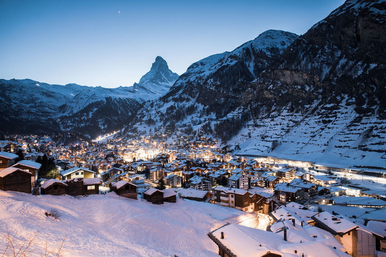 Scenic view of snowcapped mountains by townscape against clear sky during winter