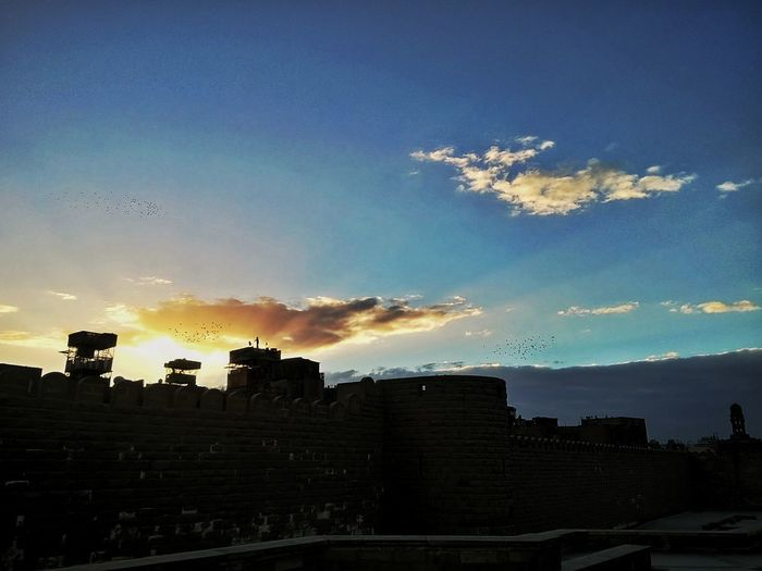 Sunset Sky Built Structure Cloud - Sky Beauty In Nature Cloud Dramatic Sky Birds Man Capture The Moment Alone Sun Blue Traveling Home For The Holidays Citadel Egypt Dramatic Edit Dramatic Clouds Bird Call EyeEmNewHere