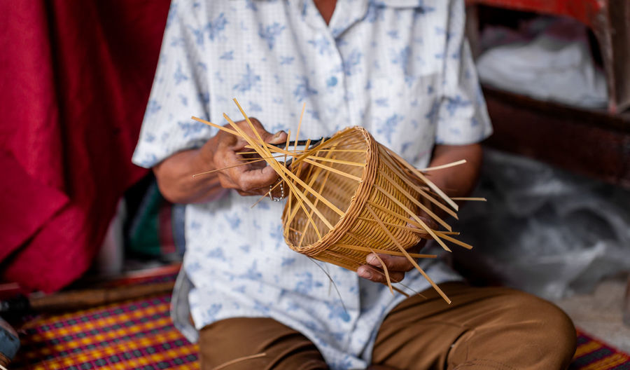 Midsection of man making wicker in workshop