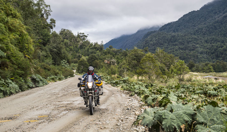 Man riding bicycle on road against mountains