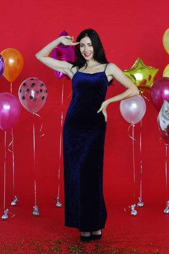 Full length of woman standing with red balloons