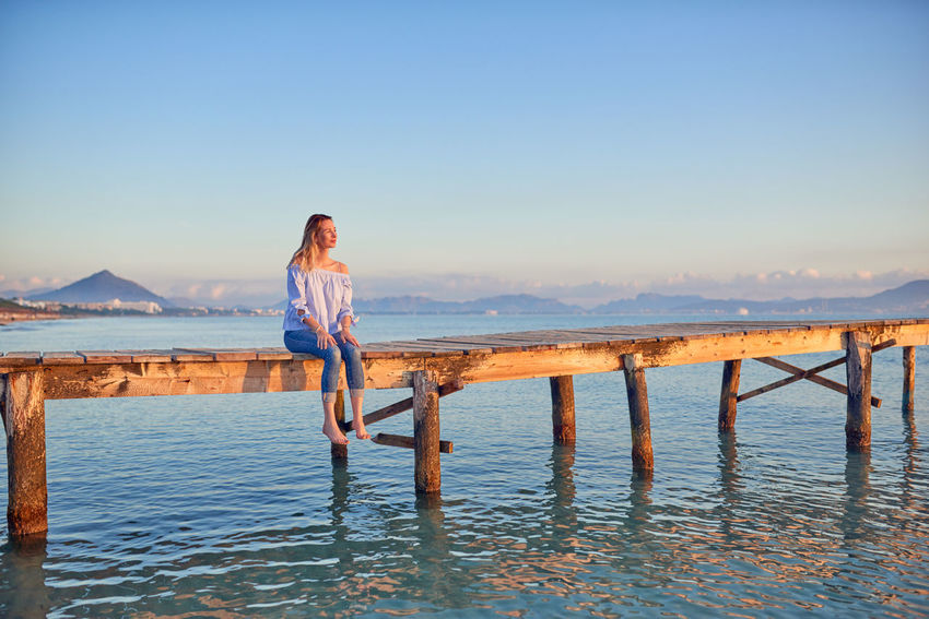 Barefoot woman sitting on a coastal pier at sunset Copy Space Freedom Woman Beach Beauty In Nature Best Ager Concept Day Full Length Happiness Leisure Activity Lifestyles Middle-aged Nature One Person Outdoors Real People Scenics Sea Sky Standing Sunrise Sunset Vacations Water