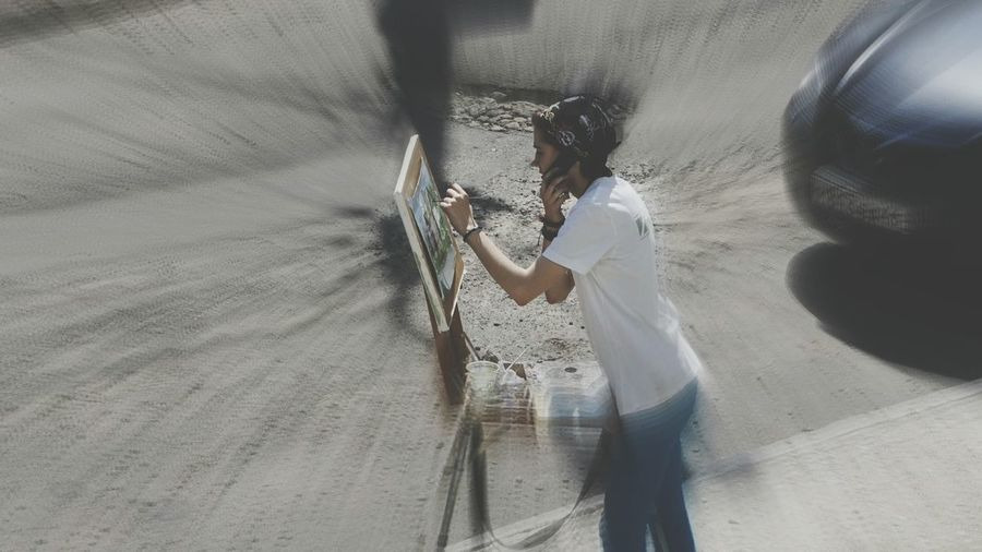 High Angle View Of Painter Painting While Talking On Phone On Street