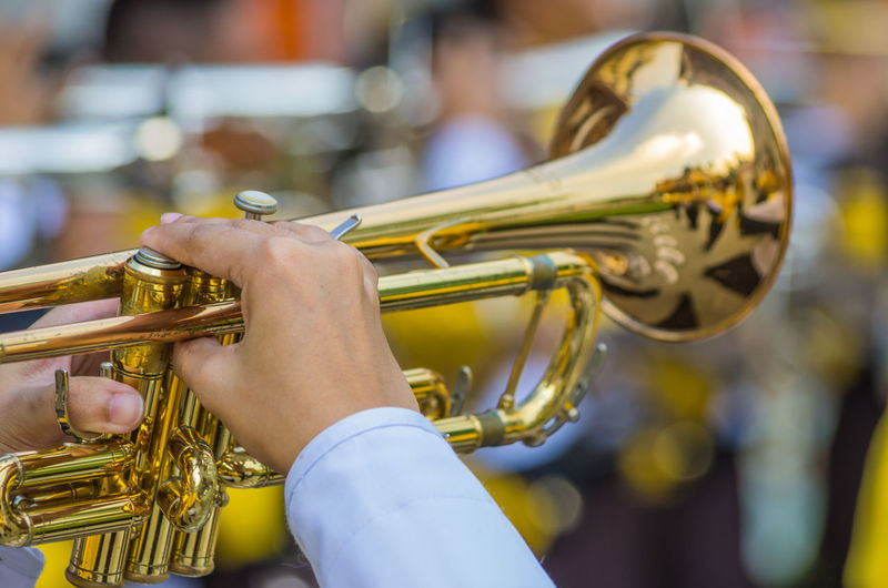 Cropped hands of musician playing trumpet during music festival