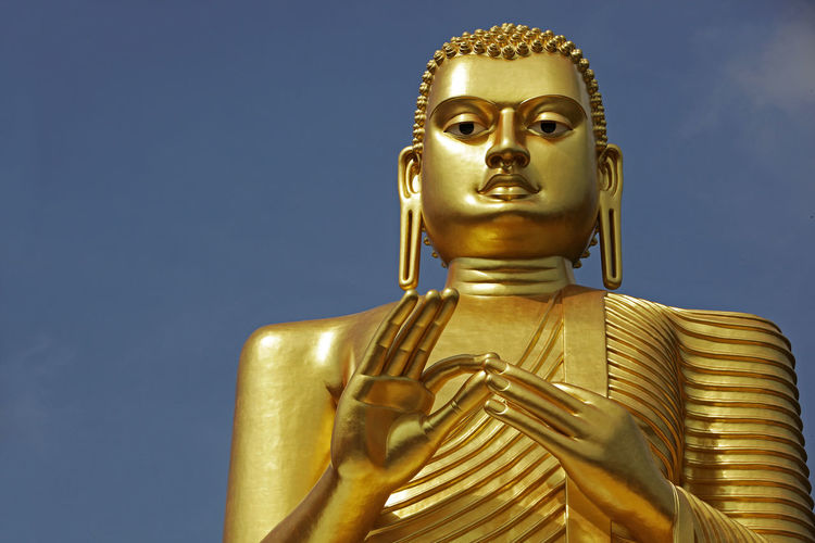 Buddha Copy Space Architecture Art And Craft Belief Craft Creativity Dharmachakra Gold Gold Colored Human Representation Idol Low Angle View Male Likeness Metal No People Religion Representation Sculpture Sky Spirituality Statue
