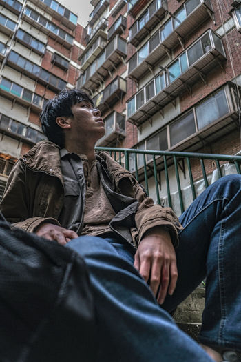 Low angle view of men sitting against building in city
