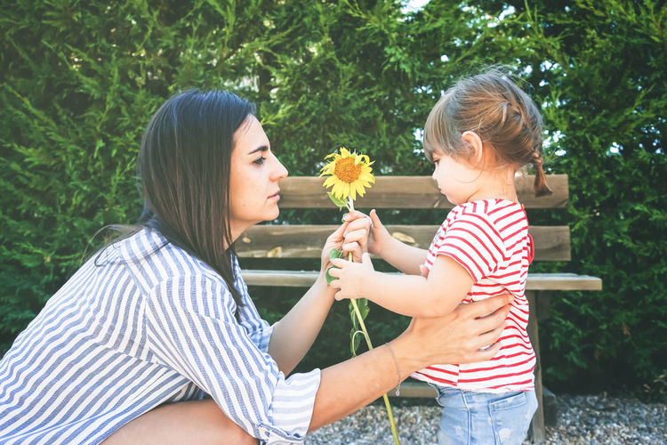 Two People Child Togetherness Bonding Plant Childhood Women Casual Clothing Real People Females Leisure Activity Lifestyles Family Girls Emotion Striped Nature Holding Flowering Plant Positive Emotion Outdoors Innocence Family Sunflower Mother