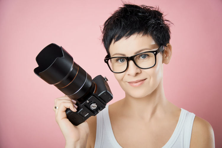 Portrait Looking At Camera Smiling Eyeglasses  Young Adult Indoors  Studio Shot One Person Front View Glasses Adult Women Colored Background Young Women Headshot Holding Happiness Cut Out Technology Beautiful Woman Camera Camera - Photographic Equipment Photographer