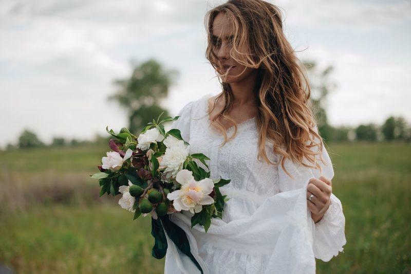 love story of young couple Adult Beautiful Woman Bouquet Bride Event Flower Flower Arrangement Flowering Plant Focus On Foreground Hair Hairstyle Long Hair Nature Newlywed One Person Outdoors Plant Standing Wedding Wedding Dress Women Young Adult Young Women