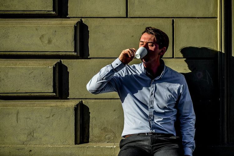 Man drinking coffee while leaning on wall