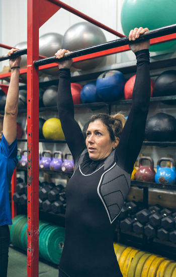 Woman hanging on exercise equipment in gym