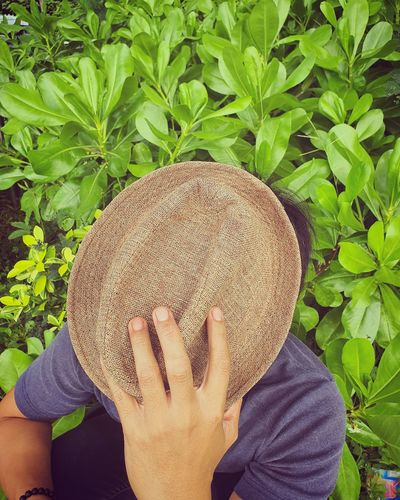 Close-up of man holding hat sitting by plants