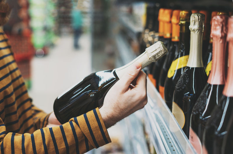 Man chooses wine at supermarket